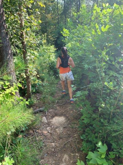 Running the tree lined and root covered Mountain to Sea trail on a recent camping trip. Wearing an orange tank, white shorts, and Orange Mud hydration vest.