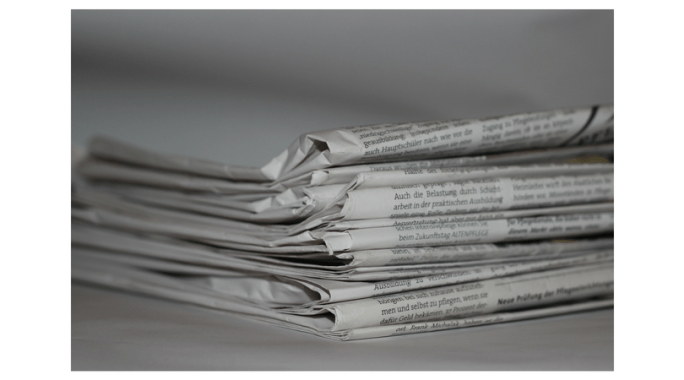 newspapers stacked on a table