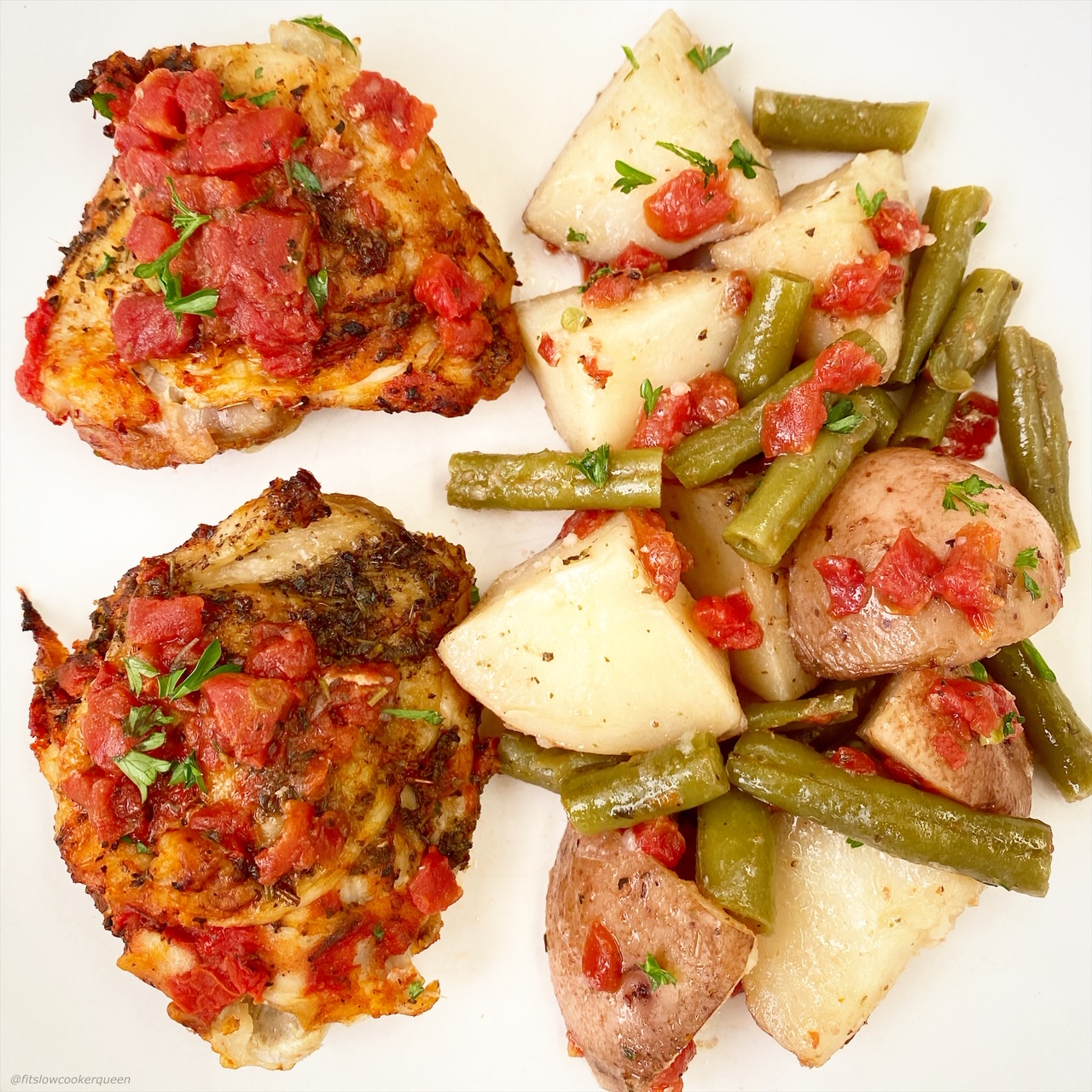 close up of 2 chicken thighs & a few scoops of potatoes & green beans.
