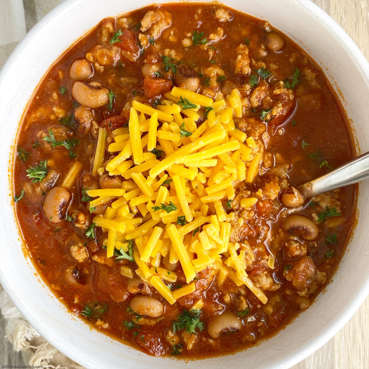 cooked soul food chili with cheese on top in a bowl