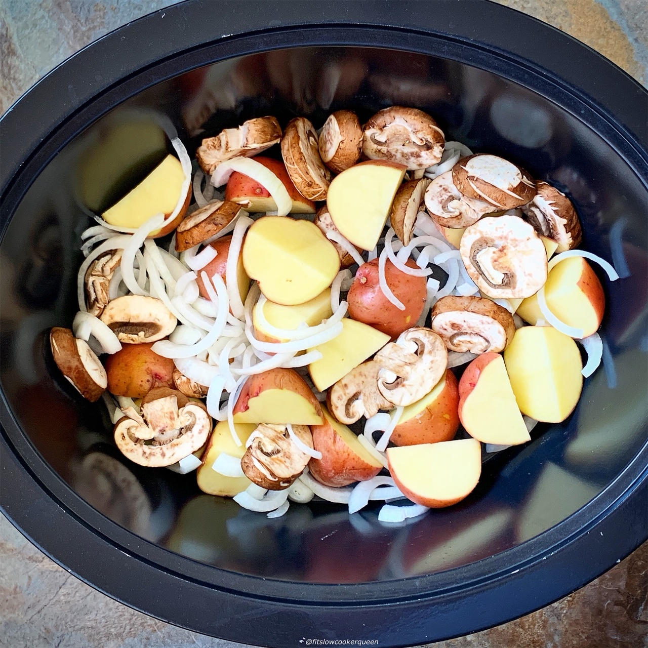 slow cooker full of potatoes, onions, and mushrooms
