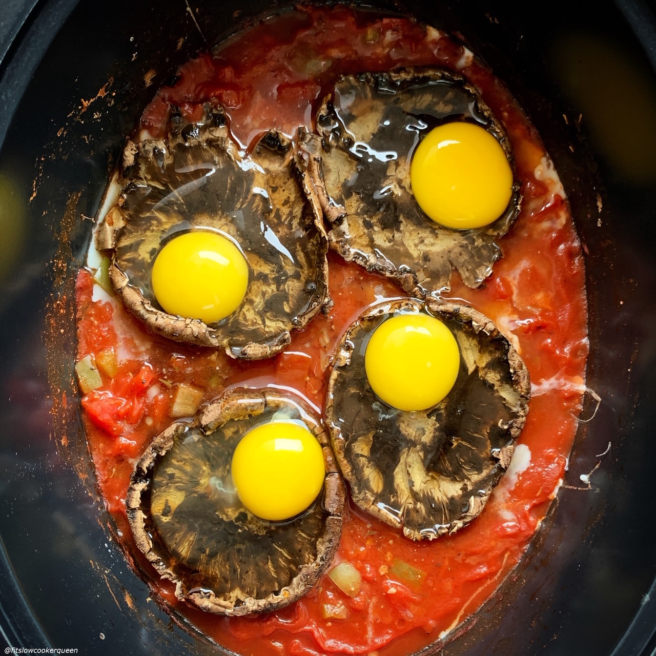 raw eggs added on top of cooked portobello mushrooms in the slow cooker