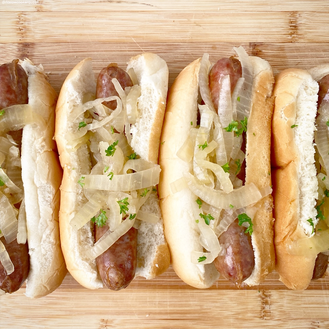lined up cooked beer brats in a bun with onions on top