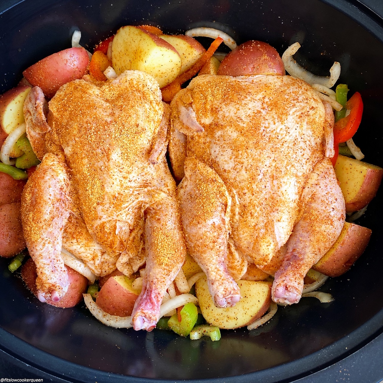 raw creole seasoned Cornish hens in the slow cooker on top of potatoes, bell peppers, celery, and onions in the slow cooker with Creole seasoning on top