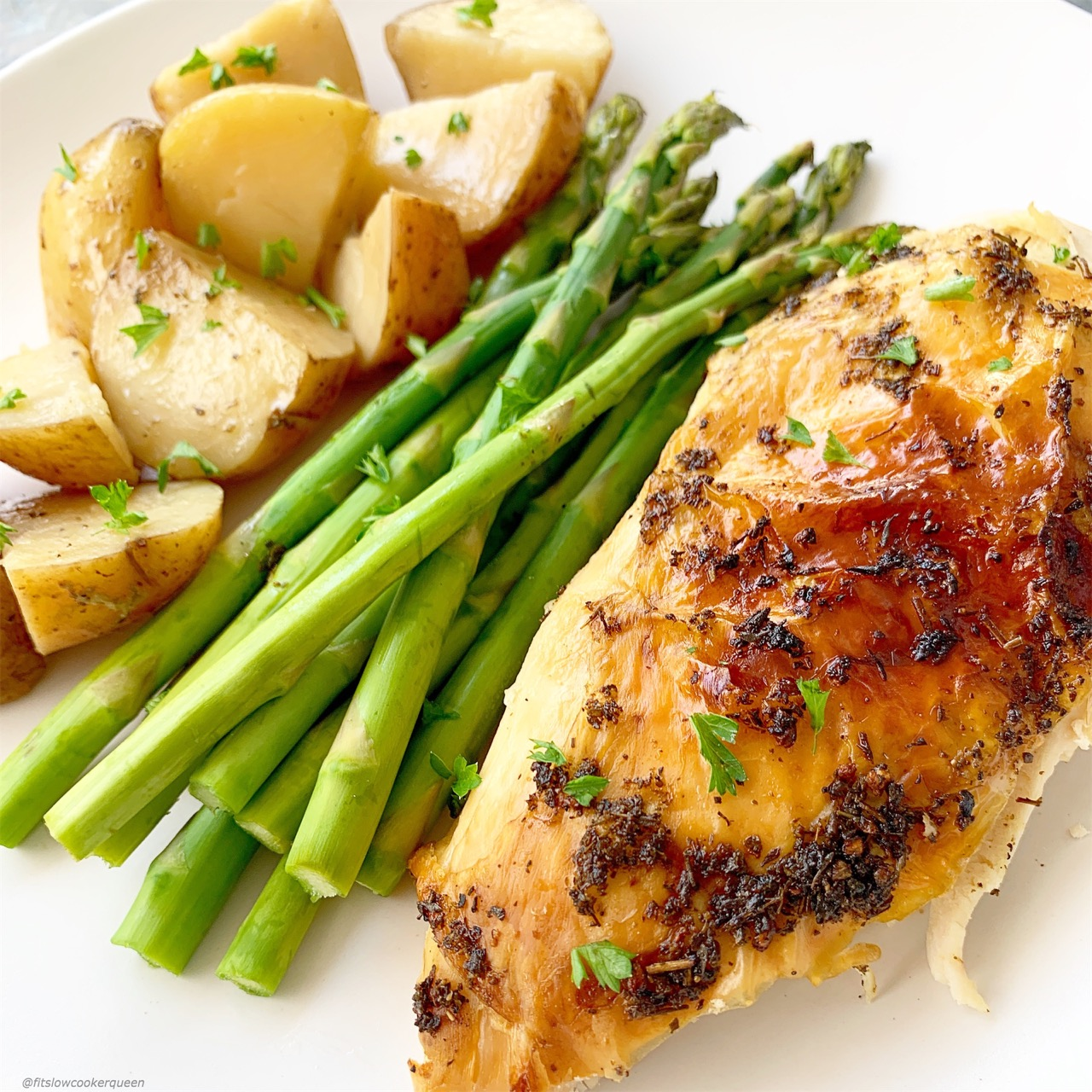 Plate of whole chicken dinner with potatoes, asparagus and chicken