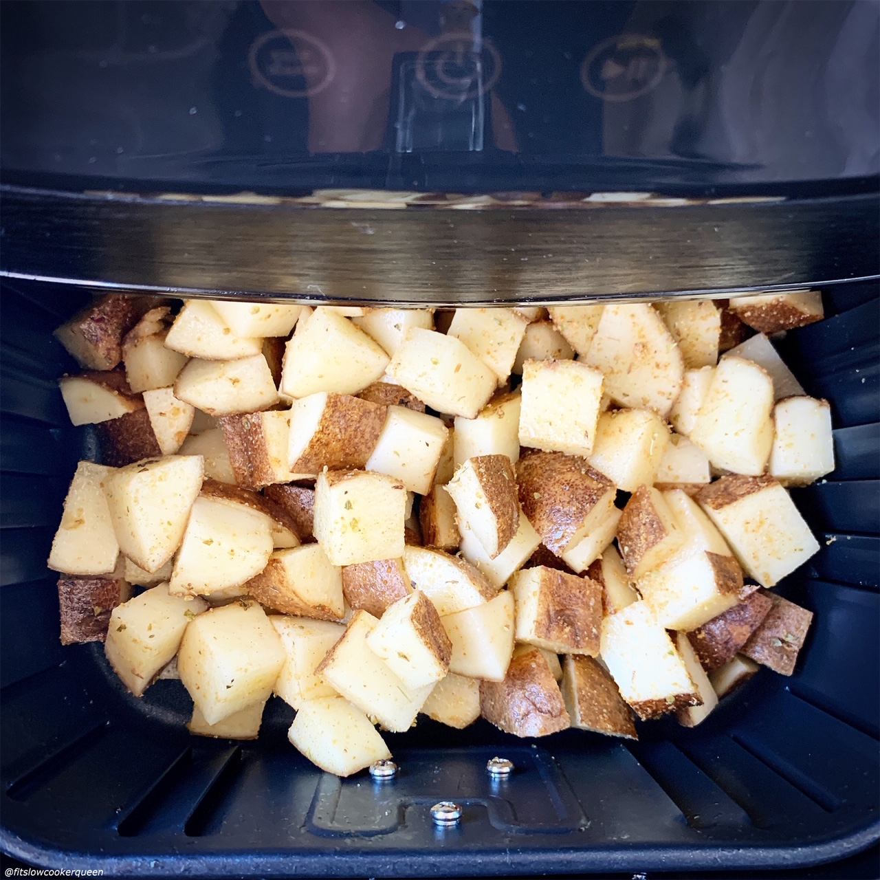 raw diced potatoes in the air fryer before cooking