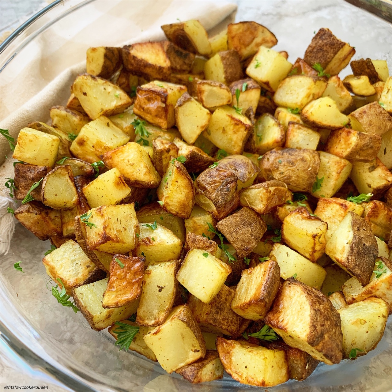 air fryer whole30 breakfast potatoes in a bowl topped with chopped parsley