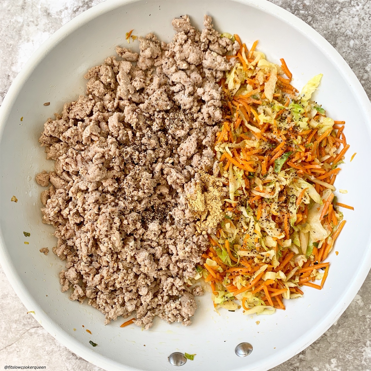 ground meat, cabbage, and carrots in a skillet with seasonings