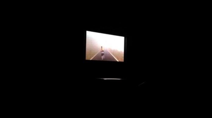 黑漆漆的停車場上播放著賽事影片