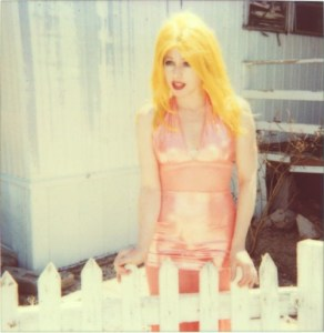 Blonde woman standing behind wooden fence.