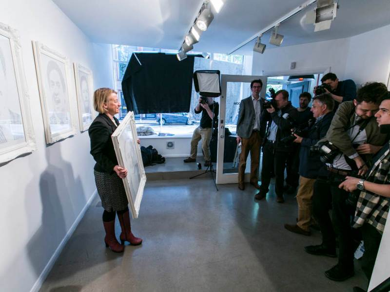 Natalie Bennett stands with framed portrait in gallery.