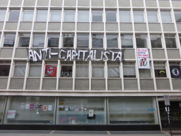 Front of building with anti-capitalist banner.