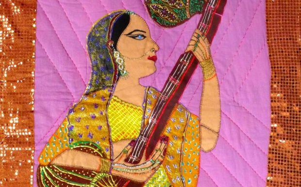 Woman sitting playing tanpura.