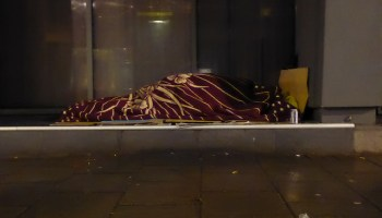 Someone sleeping on the street under a blanket.