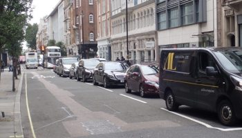 Cars and vans queuing on street.