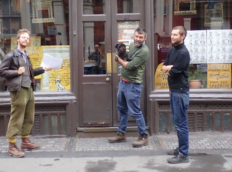 Three men and a dog outside shopfront.