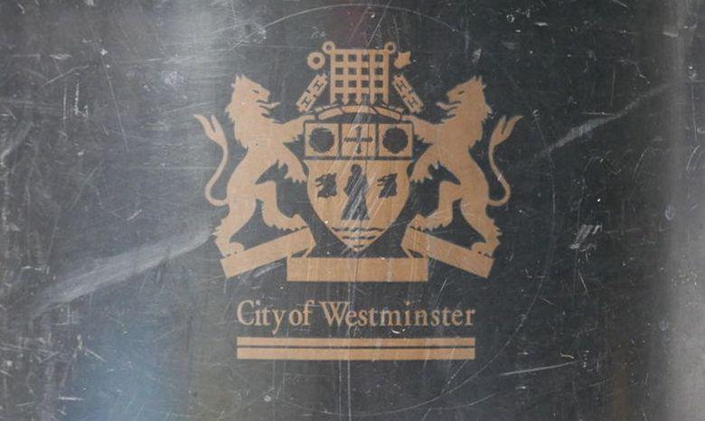 Westminster council gold logo on black bin.