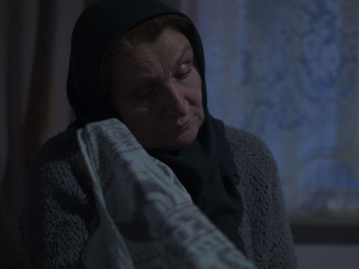 An elderly woman sitting.