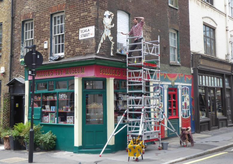 Jack Fawdry poses on the scaffolding ouside the museum and shop.