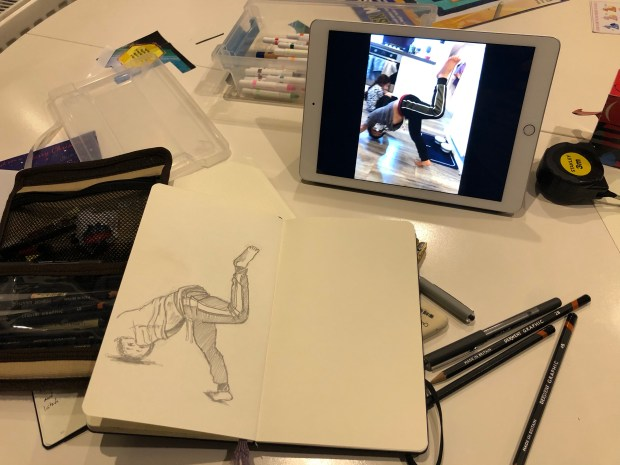 Sketchbook on table next to iPad with picture on the screen.
