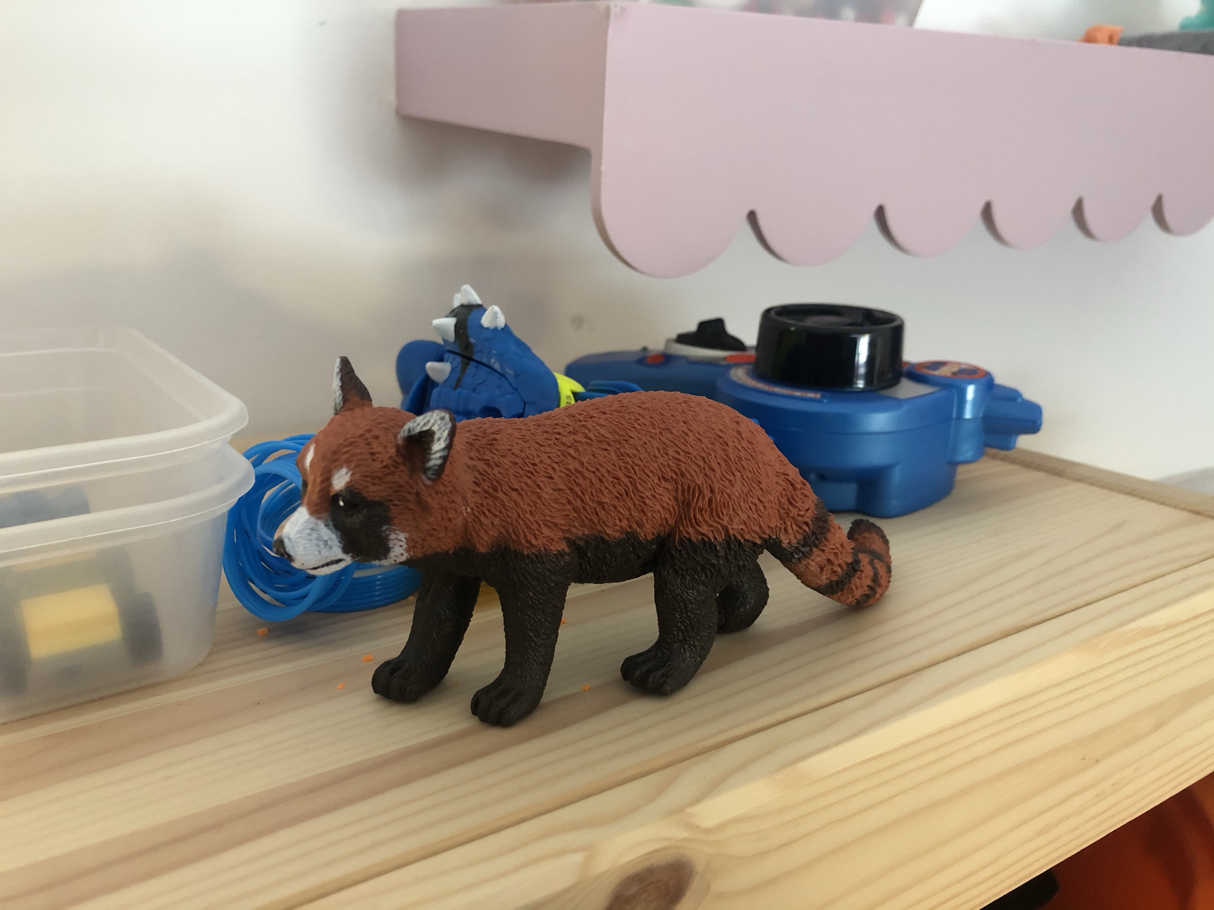 Red panda figure on a shelf with other toys.