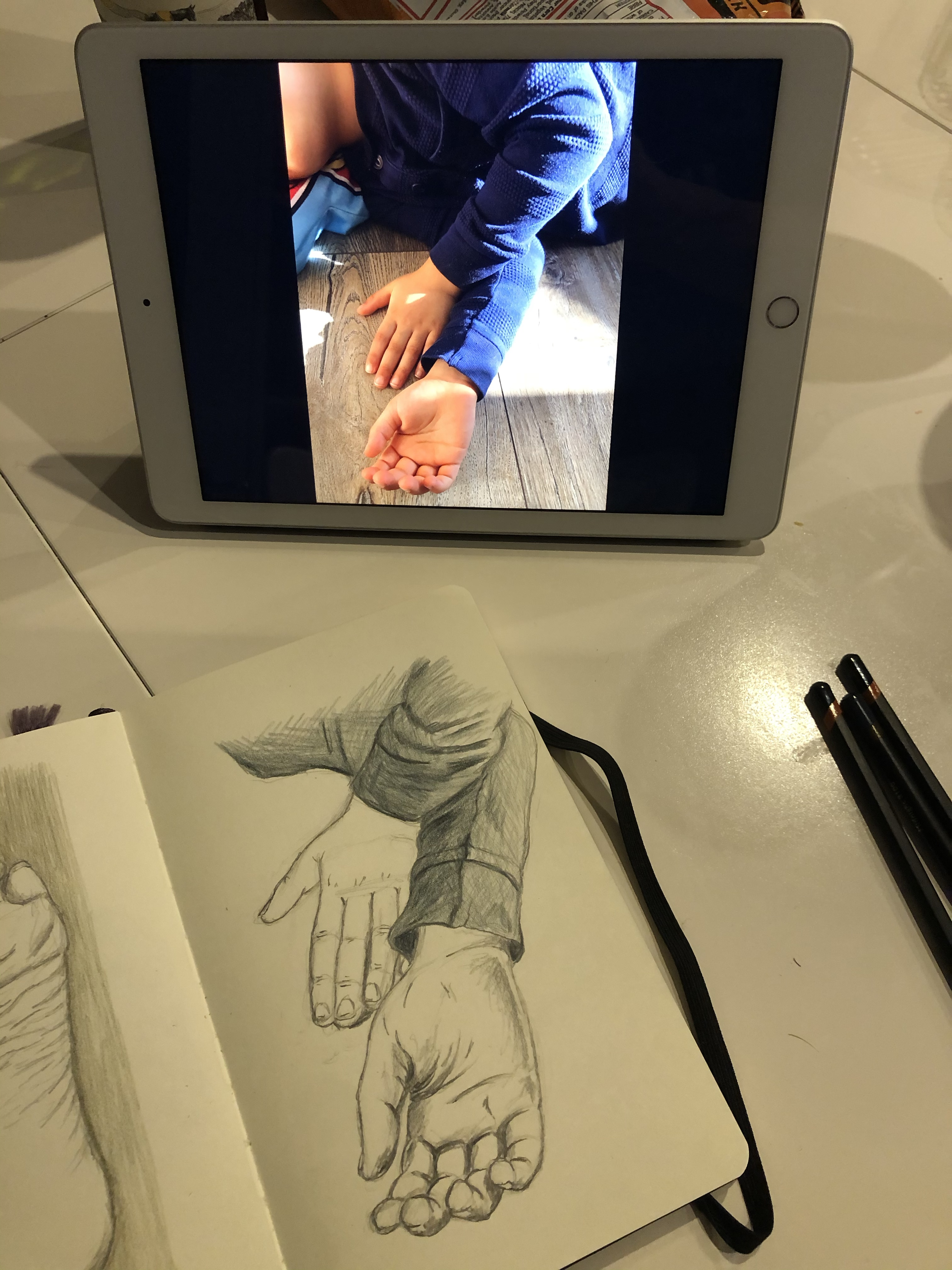 Notebook with sketch next to an iPad displaying a picture of hands.