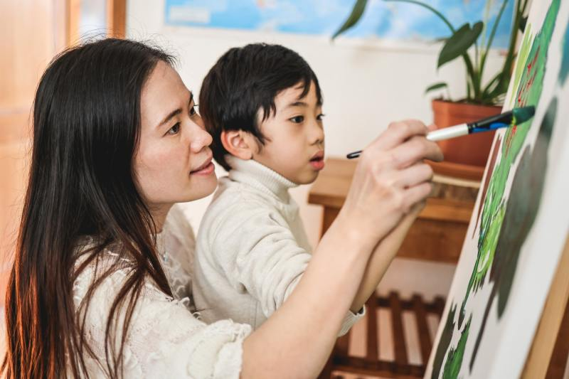 Asian kid painting on canvas during art class at home - Focus on woman eye