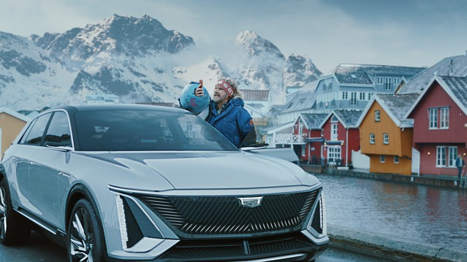 Will Ferrell stands next to a Chevy Lyriq in a Scandinavian town