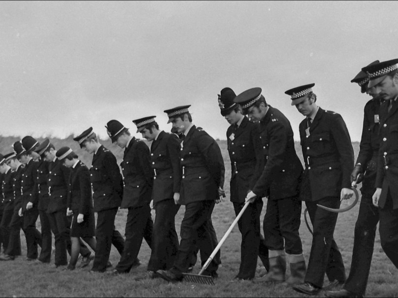A line of police officers, all looking at the ground, walk shoulder to shoulder across a field.