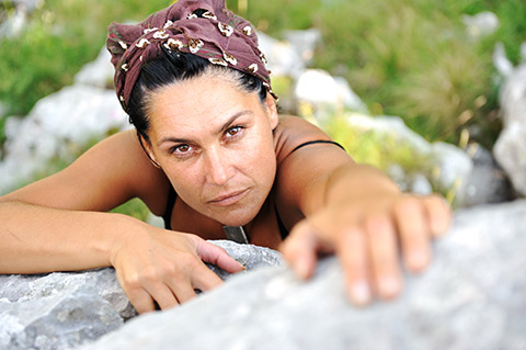 Image of woman climbing rock to illustrate getting started with influencer content marketing.