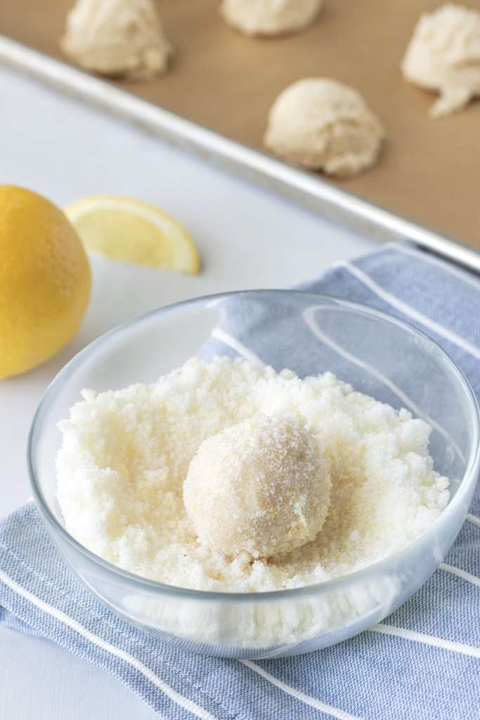 Process 1/2 cup of sugar with 1 teaspoon lemon zest and coat the dough balls in the mixture.