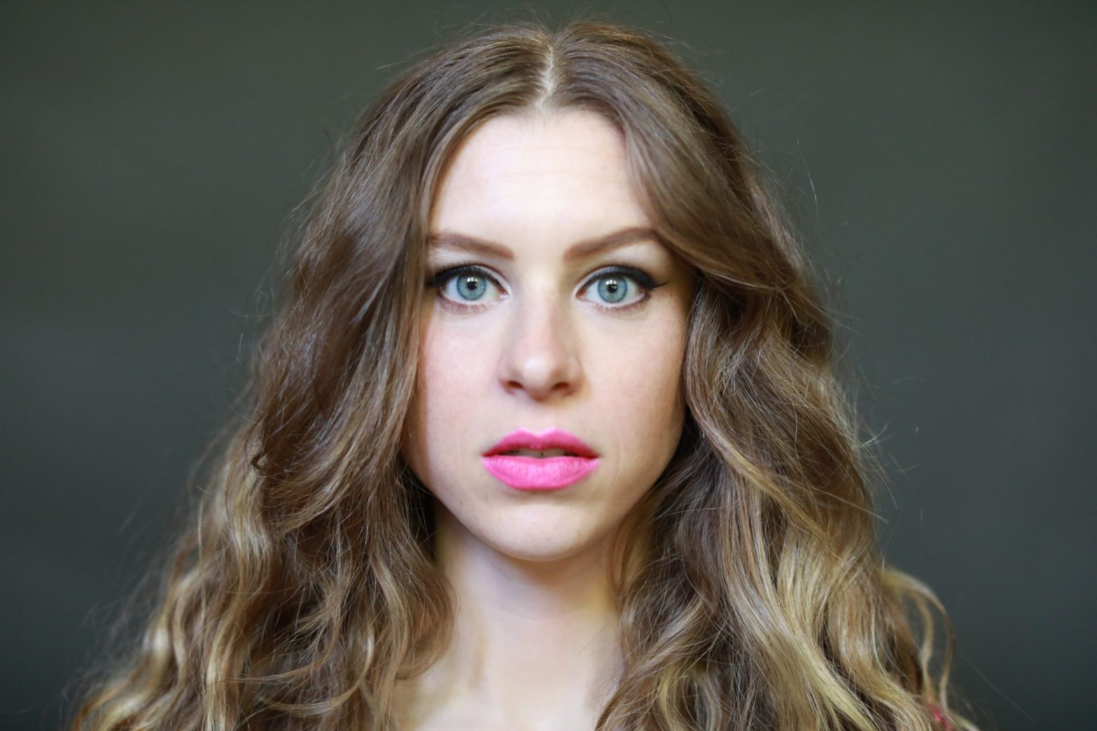 Headshot of a woman with a blank stare, afraid of being herself in relationships