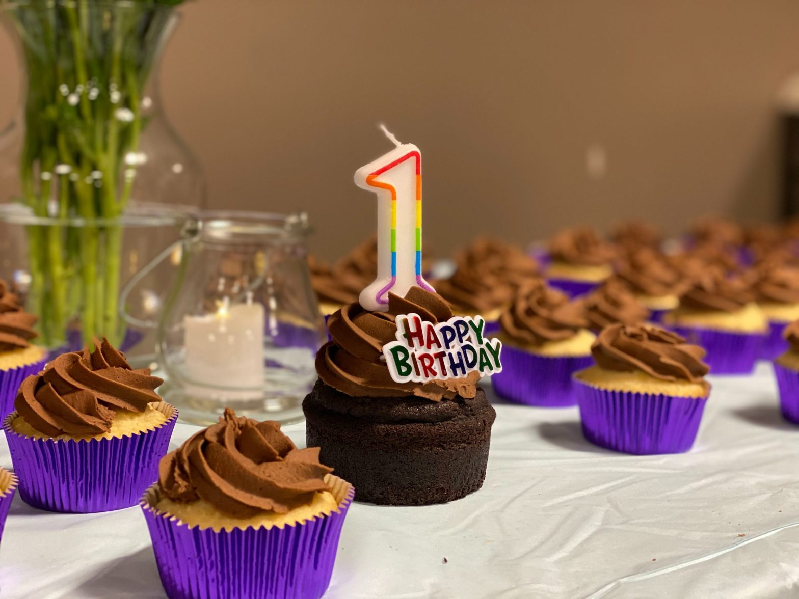 """Cupcake with a number one shaped candle that says """"Happy Birthday"""" –Fix Your Picker Turns One"""