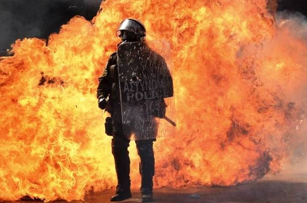 A Greek policeman stands next to a wall of flames during the anti-austerity protest