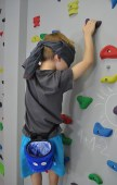 chłopiec z zawiązanymi oczami na ściance wspinaczkowej wykonuje ćwiczenia fizjoterapeutyczne