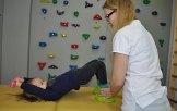 dziewczynka na bosu wykonuje ćwiczenia fizjoterapetyczne