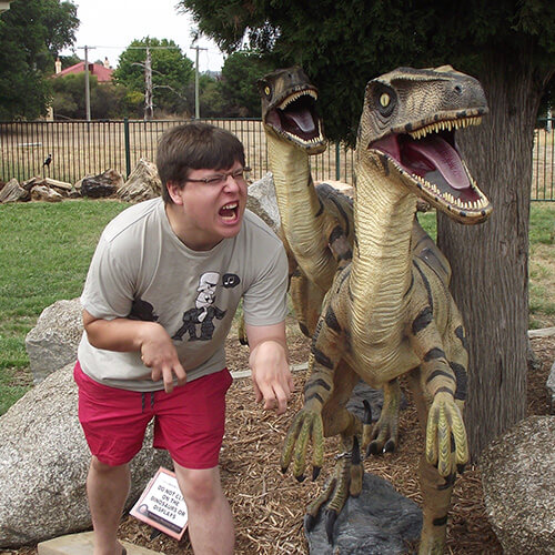 Ben standing next to two replica dinosaurs