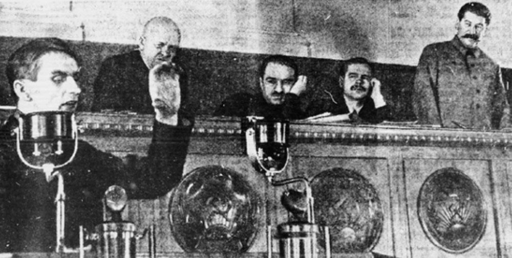 Trofim Lysenko, left, speaking at the Kremlin in 1935, with Joseph Stalin standing, right. (Wikimedia Commons)