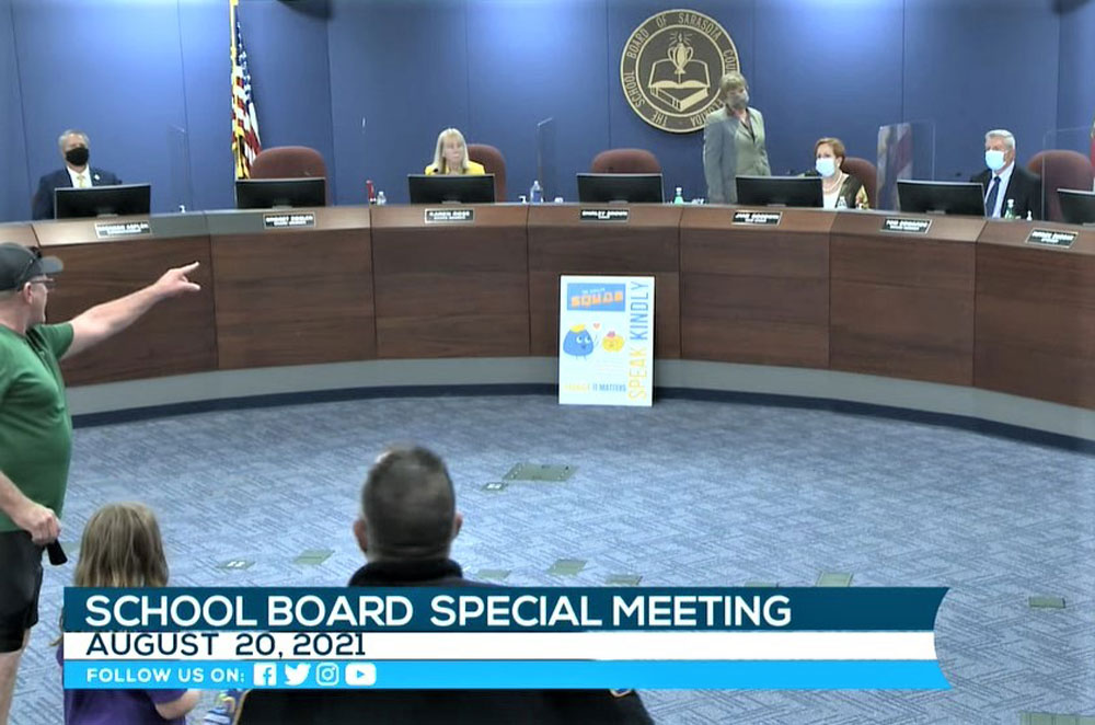 John Wilson, who opposes mask mandates, shouts at Sarasota County School Board chair and former state Rep. Shirley Brown (standing), who called a recess to clear the room of hecklers. (Sarasota County School Education Channel)