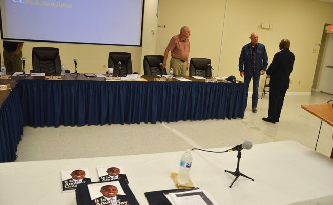 Manager candidate Alvin Jackson had laid out copies of his self-published book, 'It Is Another Great Day,' before his interview Tuesday, and distributed copies to commissioners. He spoke with Commissioners Bill Baxley, left, and Elbert Tucker. (© FlaglerLive)