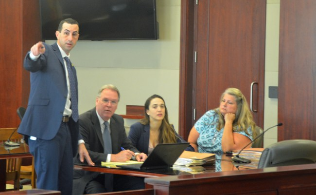 Assistant State Attorney Jason lewis, standing, with the attorneys for the defense, Kevin Kulik and Ashley, seated next to Kimberle Weeks, in blue, at today's jury selection. (c FlaglerLive)