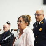 Denis Bevan, standing at the podium with Palm Coast Fire Chief, as the Palm Coast City Council was offering her the interim manager's job last Tuesday. (© FlaglerLive)