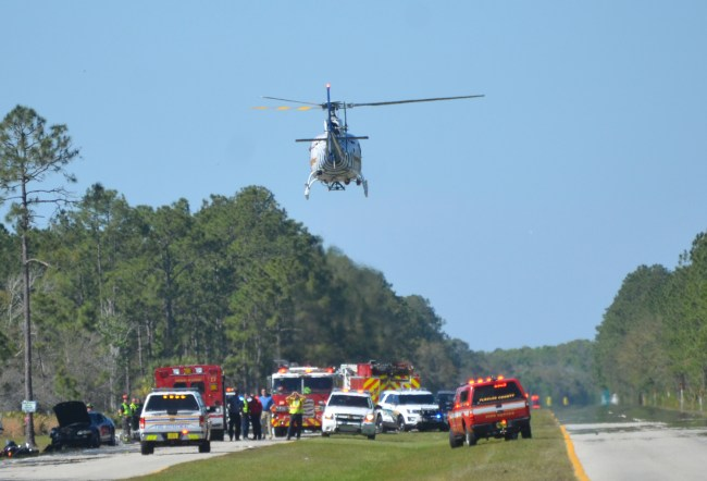 Flagler County Fire Flight, the emergency helicopetr, lifts off from the southbound lanes of U.S. 1, north of Matanzas Woods Parkway, with one of the men seriously injured in a crash with the driver of a car at around 3:35 this afternoon. Click on the image for larger view. (c FlaglerLive)