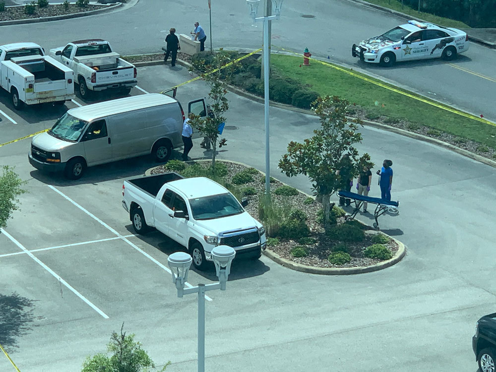 The scene at the courthouse parking lot, within view of the Government Services Building and of courtrooms, some of them in session, in late morning as the Medical Examiner was preparing to remove the victim. (© FlaglerLive)