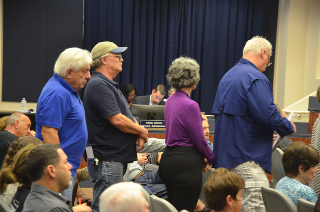 County Administrator Craig Coffey, sitting in the center, as a dozen people lined up at the beginning of today's County Commission meeting to speak largely in opposition to recent Coffey-initiated proposals. (c FlaglerLive)