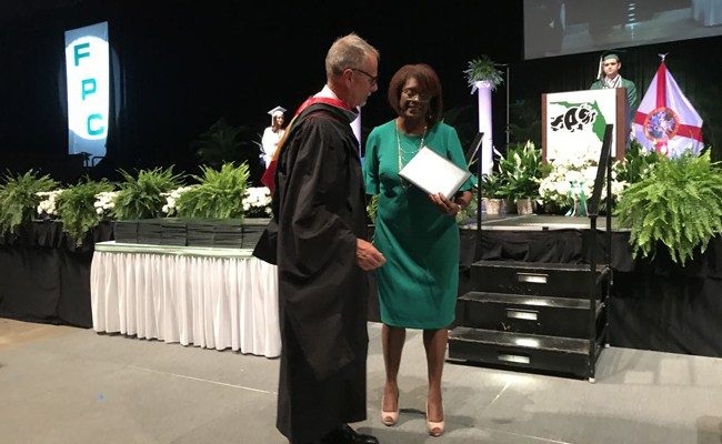 Carmen Gray receiving an honorary degree for her late son Curtis from Superintendent Jim Tager Thursday evening at the Ocean Center. Gray would have been part of Flagler Palm Coast High School's Class of 2019. (Jason Wheeler)