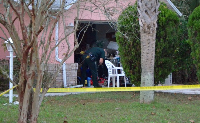 A Flagler County Sheriff's deputy examines the garage where deputies had earlier that day shot and killed Troy Gordon, a 32-year-old resident of the house. (© FlaglerLive)
