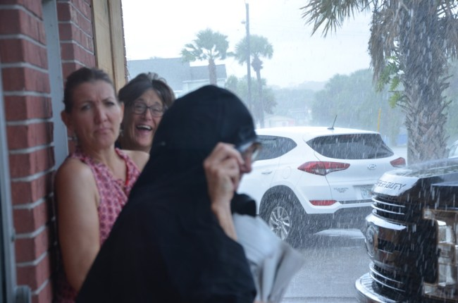Anna Hackett, center, and others caught in a pre-Dorian downpour outside Swillersbees in Flagler Beach Sunday. (© FlaglerLive)