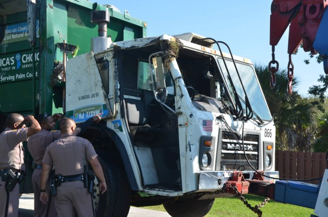 The driver's side of the Waste Pro truck shortly after the truck was set back on its wheels. Click on the image for larger view. (© FlaglerLive)