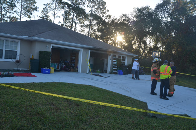 The owner of the house, Jessica Evans, is comforted by a friend, Richard Price, the Palm Coast attorney, as Deputy Fire Chief Jerry Forte, right, speaks with Battalion Chief Ron Petrillo and Fire Police Captain Steve Garnes. (© FlaglerLive)
